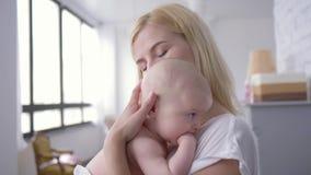 La mère embrasse doucement un bébé nouveau-né, portrait de jeune femme heureuse tenant une petite fille et regardant la caméra banque de vidéos