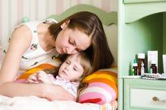 La mère embrasse l'enfant malade photos stock