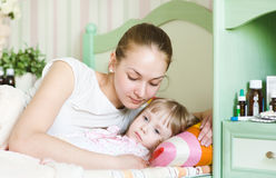 La mère embrasse l'enfant malade photographie stock