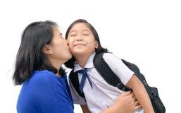 La mère embrassent sa fille dans l'étudiant uniforme Image stock