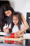 La mère enseigne le descendant à faire cuire Photographie stock