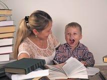 La mère enseigne le fils à lire parmi les piles de livres photo stock