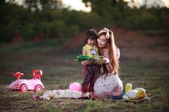 La mère enseigne le livre de lecture à la fille Photographie stock libre de droits