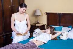 La mère enseigne sa fille à lire Les relations entre paren Photographie stock libre de droits
