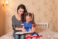 La mère enseignent à lire sa petite fille Photo stock