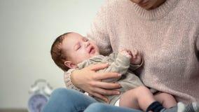 La mère essayant de calmer le bébé pleurant, problème colique infantile cause la dépression de parent images stock