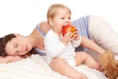 La mère est endormie et l'enfant mange Photo stock
