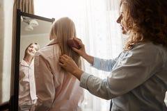 La mère est sa ferme l'ami Jeune fille européenne tenant le miroir proche dans les chemises de nuit, regardant elle-même et le so Photo stock