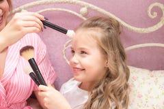 La mère et la fille appliquent le maquillage ensemble photographie stock