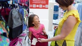 La mère et la fille caucasiennes près font des emplettes des étagères choisissant le sac à dos de sac d'école sur le marché de me banque de vidéos