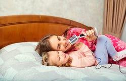 La mère et la fille chantent des chansons de karaoke d'amusement ensemble dans la chambre photographie stock libre de droits