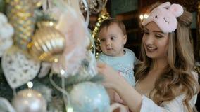 La mère et la fille décorent et admirent un arbre de Noël banque de vidéos