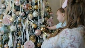 La mère et la fille décorent et admirent un arbre de Noël clips vidéos