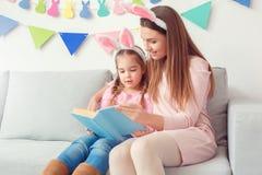 La mère et la fille dans des oreilles de lapin weekend ensemble à la maison se reposer Image stock