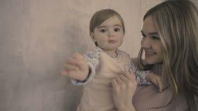 La mère et la fille de brune restent dans le studio près du mouvement lent de mur gris banque de vidéos