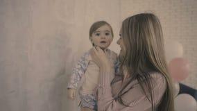 La mère et la fille de brune restent dans le studio près du mouvement lent de mur gris clips vidéos