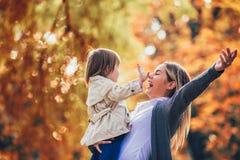 La mère et la fille en parc appréciant le bel automne se garent photographie stock libre de droits