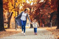 La mère et la fille en parc appréciant le bel automne se garent images stock