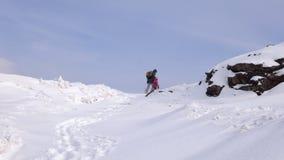 La mère et la fille escaladent la colline sur un chemin neigeux un jour froid d'hiver banque de vidéos