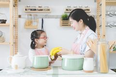 La mère et la fille font cuire ainsi qu'un visage de sourire dans la cuisine en bois moderne, avec des ustensiles de cuisine et l photos stock
