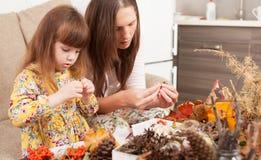 La mère et la fille font des poupées à partir des matériaux naturels photos stock