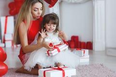 La mère et la fille heureuses analyse des cadeaux le jour du ` s de Valentine Photographie stock