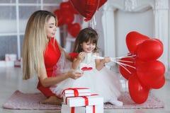 La mère et la fille heureuses analyse des cadeaux le jour du ` s de Valentine Photos stock