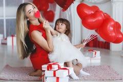 La mère et la fille heureuses analyse des cadeaux le jour du ` s de Valentine Photo libre de droits