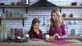 La mère et la fille s'asseyent sur la table de cuisine et des biscuits de consommation avec du café banque de vidéos