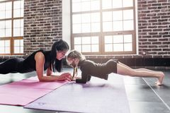 La mère et la fille se tenant dans la planche de dauphin posent, phalankasana, pendant la session de yoga au centre de fitness image libre de droits