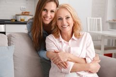 La mère et la fille weekend ensemble à la maison étreindre regardant l'appareil-photo Photos libres de droits