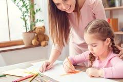 La mère et la fille weekend ensemble à la maison le dessin de observation de fille de maman de concept d'éducation Photographie stock libre de droits