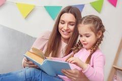 La mère et la fille weekend ensemble à la maison se reposer lisant le conte de fées Photos stock