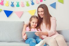 La mère et la fille weekend ensemble à la maison se reposer tenant les bandes dessinées de observation de comprimé numérique Image libre de droits