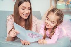 La mère et la fille weekend ensemble à la maison sur des félicitations de lecture de sofa Images libres de droits