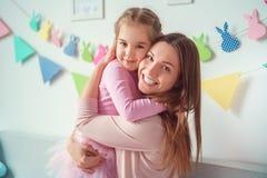 La mère et la fille weekend ensemble à la maison sur le sofa étreignant regardant le sourire d'appareil-photo Photos stock