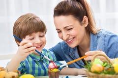La mère et l'enfant heureux de sourire apprécient en peignant des oeufs de pâques images stock