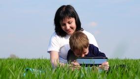 La mère et l'enfant passent le temps se reposant sur l'herbe verte et le film des enfants de observation sur la tablette banque de vidéos