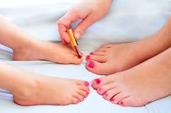 La mère et l'enfant peignent leurs pieds avec le vernis à ongles Images libres de droits