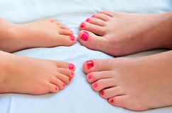 La mère et l'enfant peignent leurs pieds avec le vernis à ongles Photos stock
