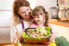 La mère et l'enfant regardent très le plat disposé de Image stock