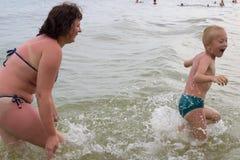 La mère et l'enfant sur la mer éclabousse Photo libre de droits