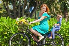 La mère et la fille allant à vélo le long du sable de mer échouent Images libres de droits