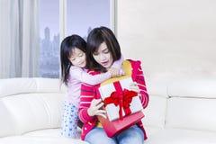 La mère et la fille attirantes ouvrent un cadeau sur le sofa Photos libres de droits