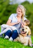 La mère et la fille avec le chien d'arrêt sont sur l'herbe image libre de droits