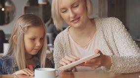 La mère et la fille choisissent des boissons au café clips vidéos