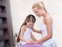 La mère et la fille communiquent dans la salle de bains Images libres de droits