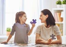 La mère et la fille font des puzzles Images libres de droits