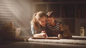 La mère et la fille heureuses de famille ont lu un livre dans la soirée photos stock