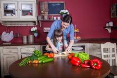 La mère et la fille heureuses ont plaisir à faire et avoir le repas sain ensemble à leur cuisine Photographie stock libre de droits